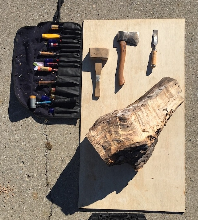 Woodworking tools including a chisel and mallet displayed next to a piece of salvaged wood