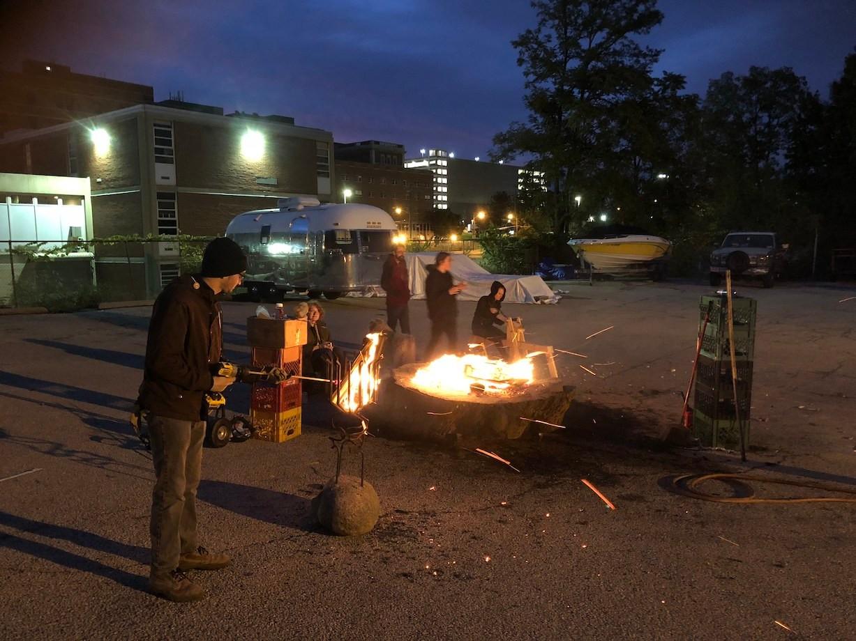 Students work in the dark around a fire