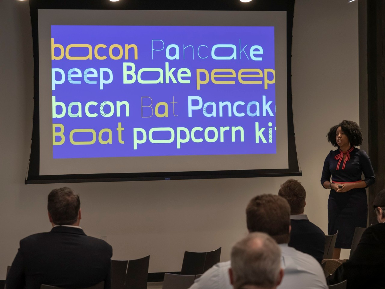A woman speaks in front of a large video screen that displays white and yellow words on a blue screen.