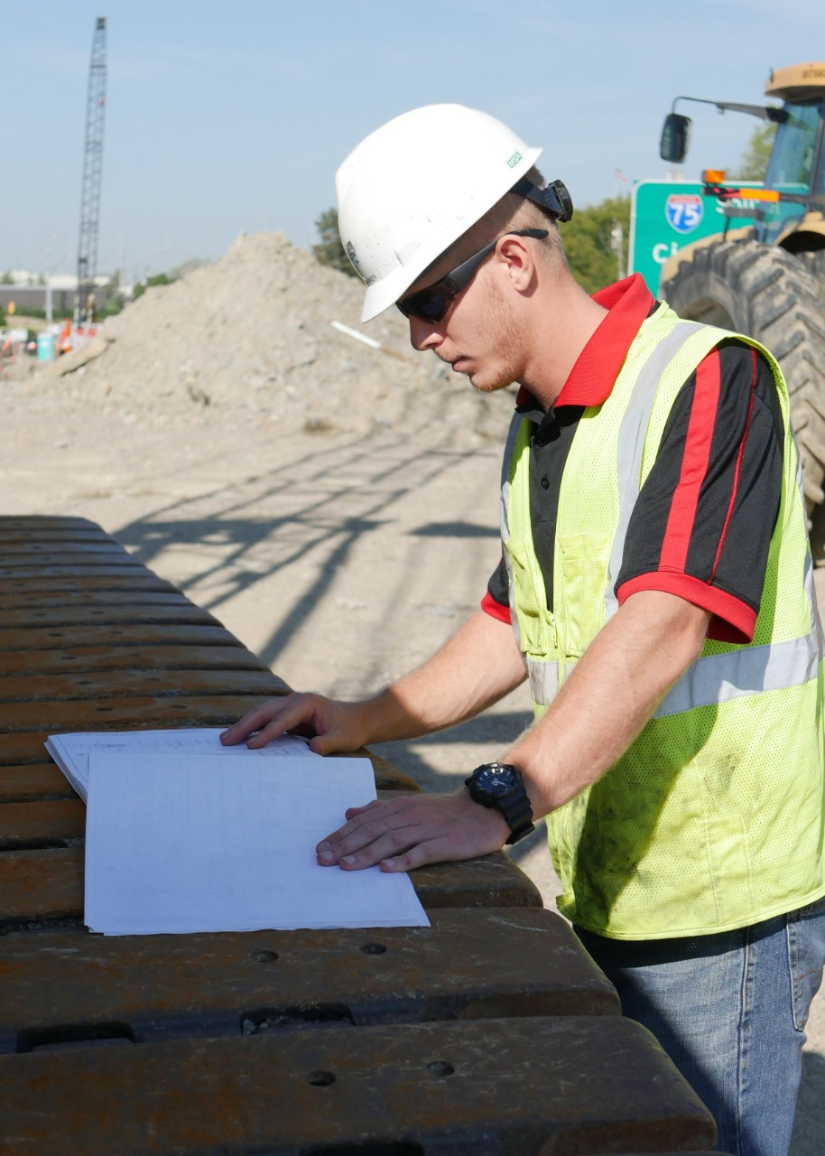 Nicewaner looks at blueprints on construction site.