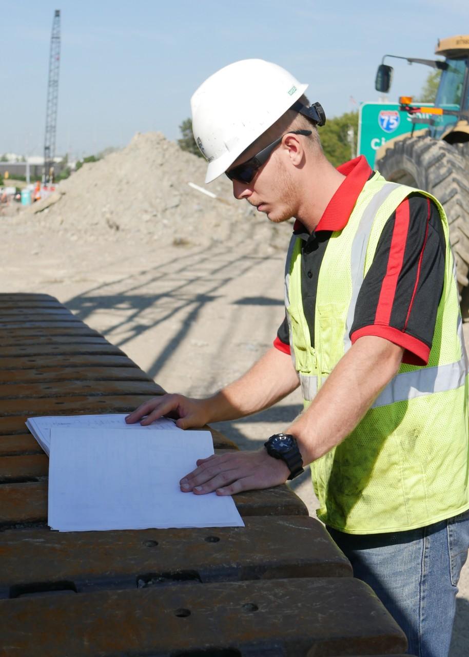 Nicewaner looks at blueprints on construction site.