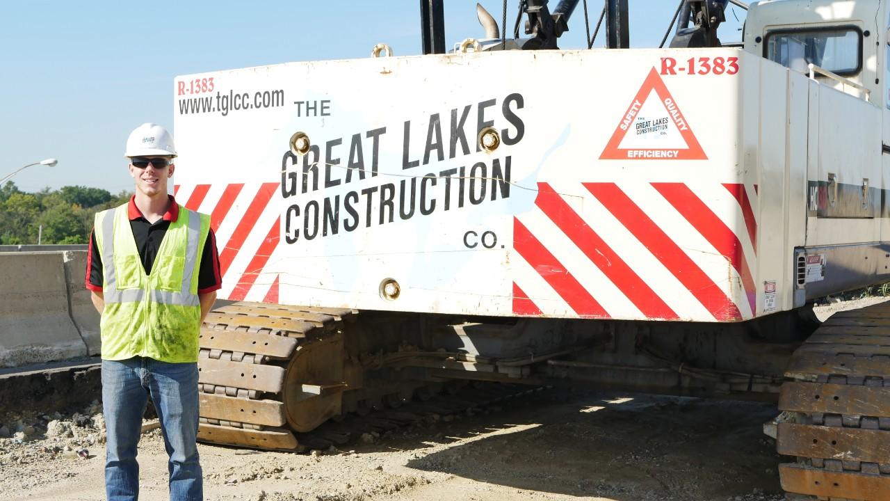 Niecwaner stands in front of construction vehicle.