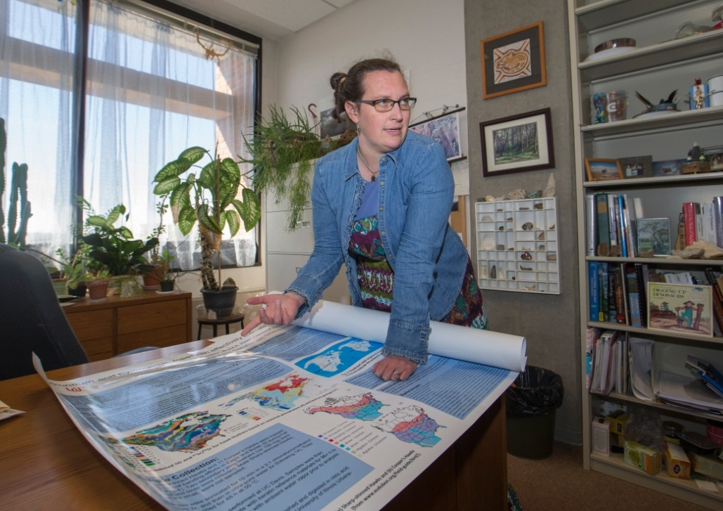 UC professor Brooke Crowley leans over her research poster spread out like a map on her desk.