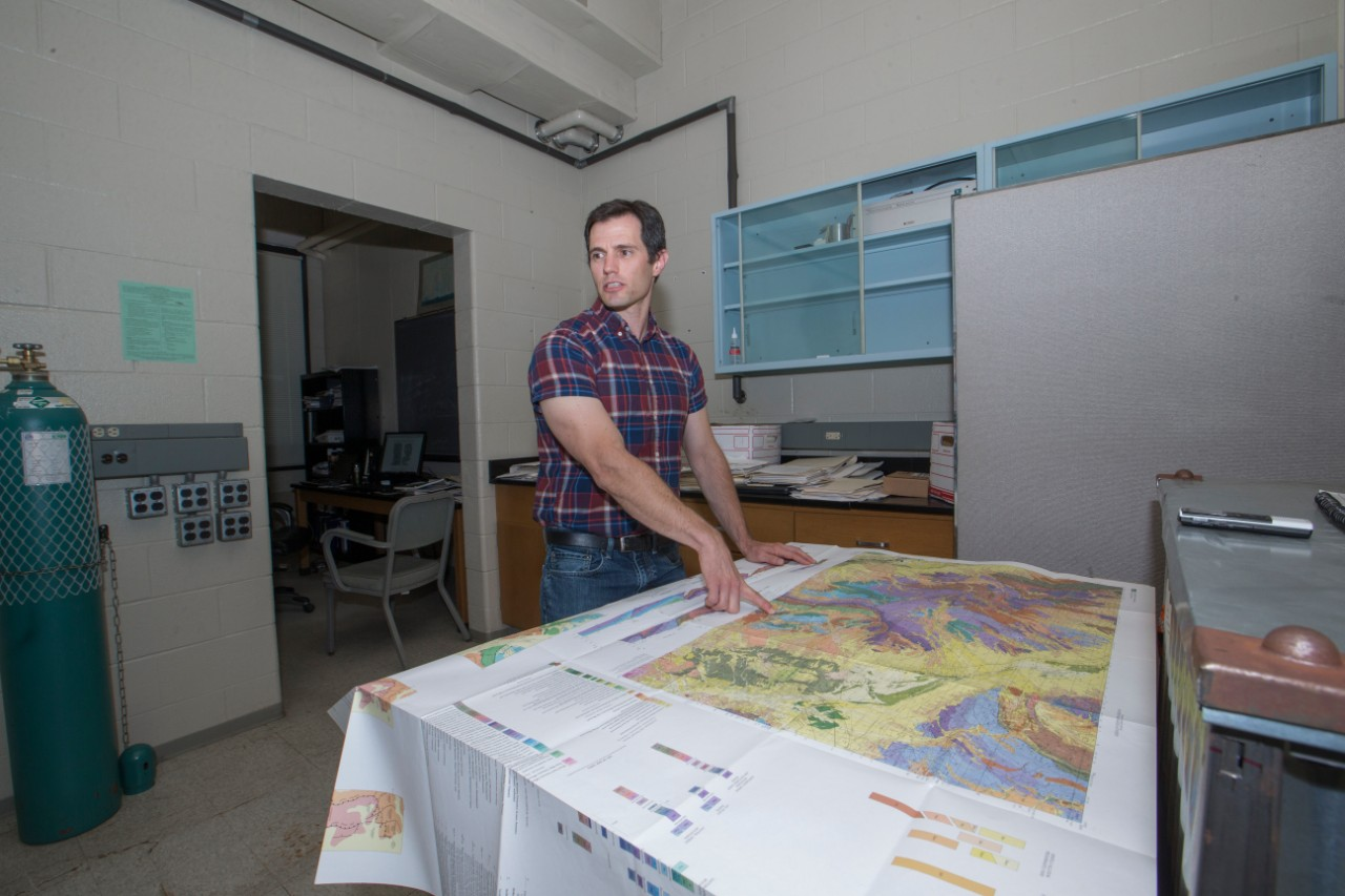 Geologist Daniel Sturmer stands over a map showing the geology of Nevada's Basin and Range.