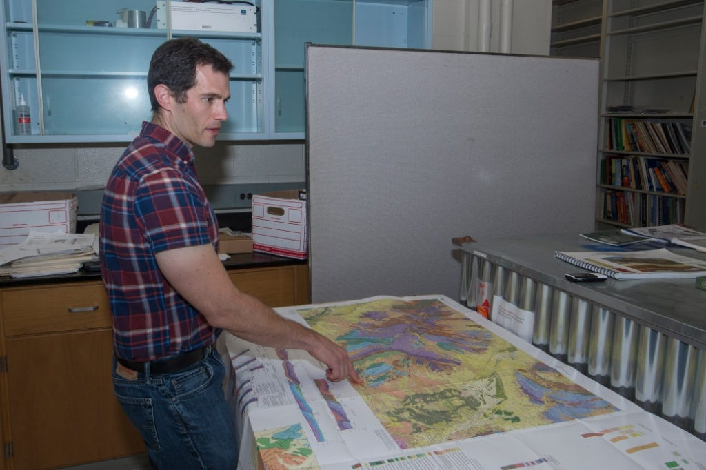 Daniel Sturmer stands over a map in his geology lab.