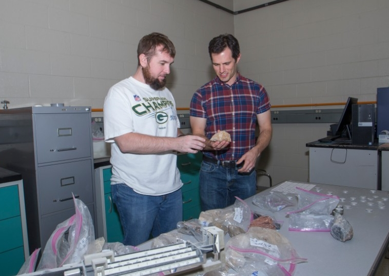 UC student Nicholas Ferry and UC professor Daniel Sturmer stand together looking at a rock specimen.