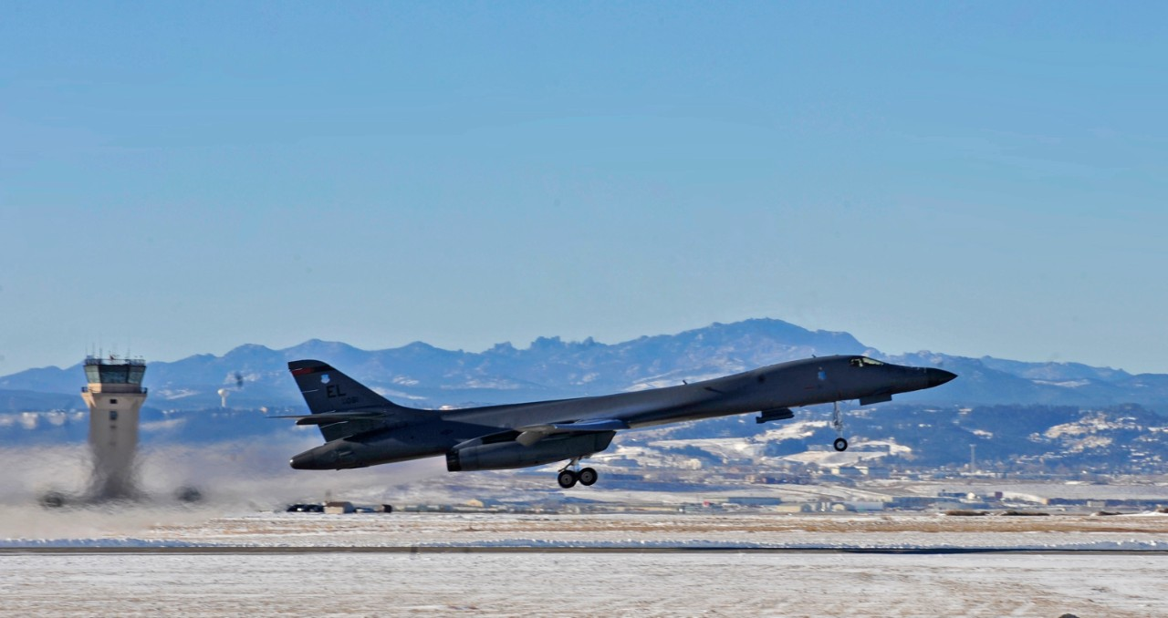 B-1B aircraft taking off with mountains in background.