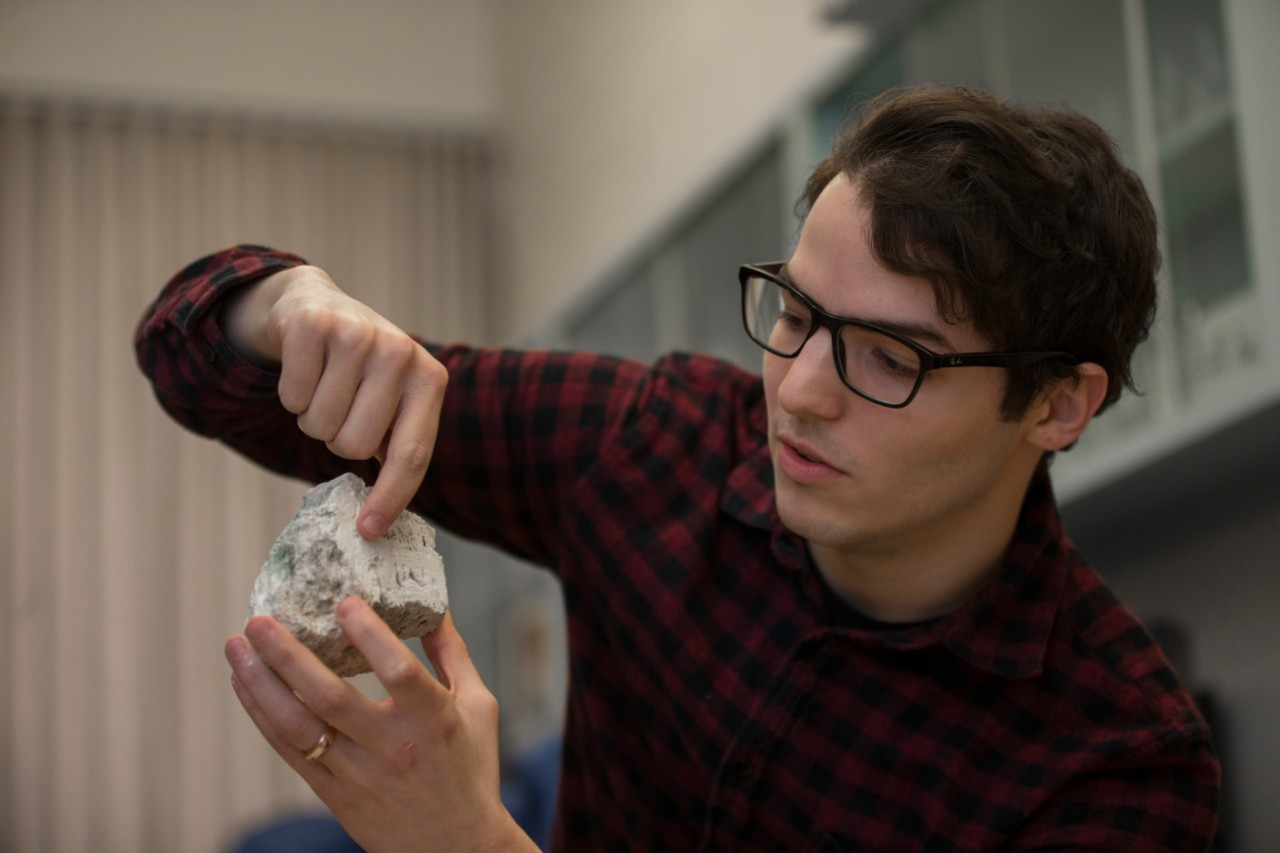 UC student Andrew Gangidine holds up and gestures to a layered rock.