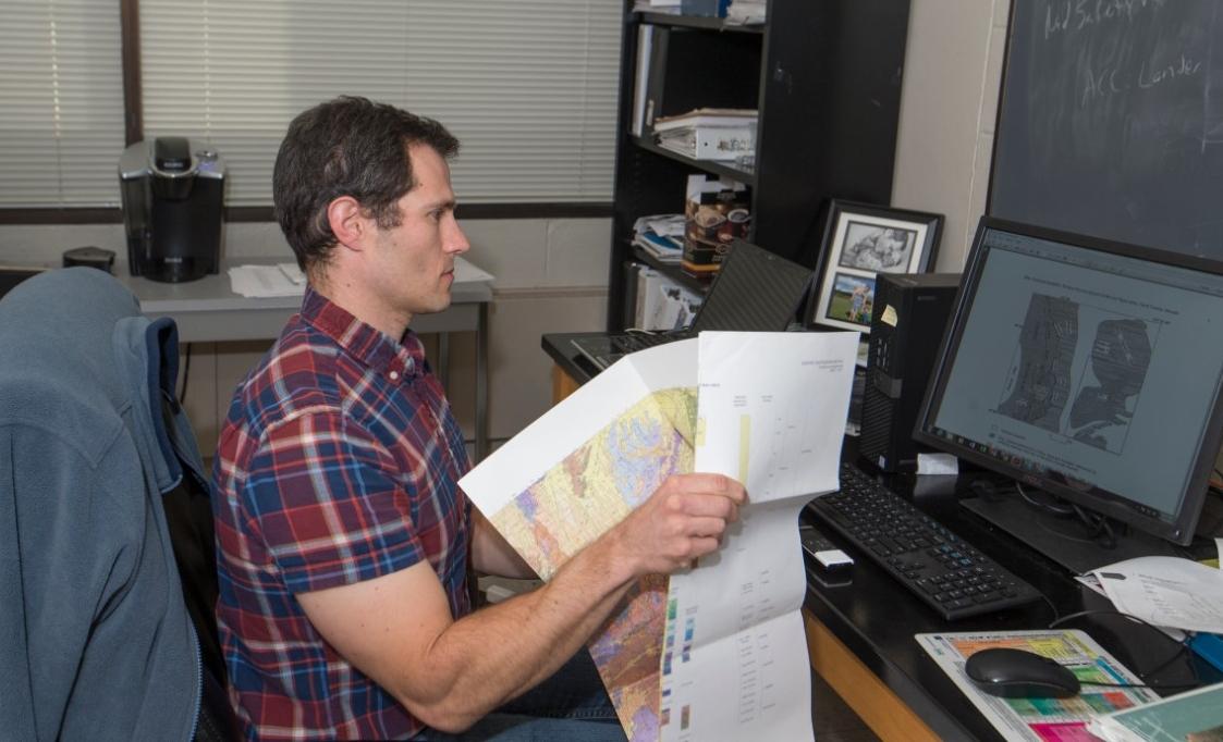 UC professor Daniel Sturmer unfolds a map in his lab.