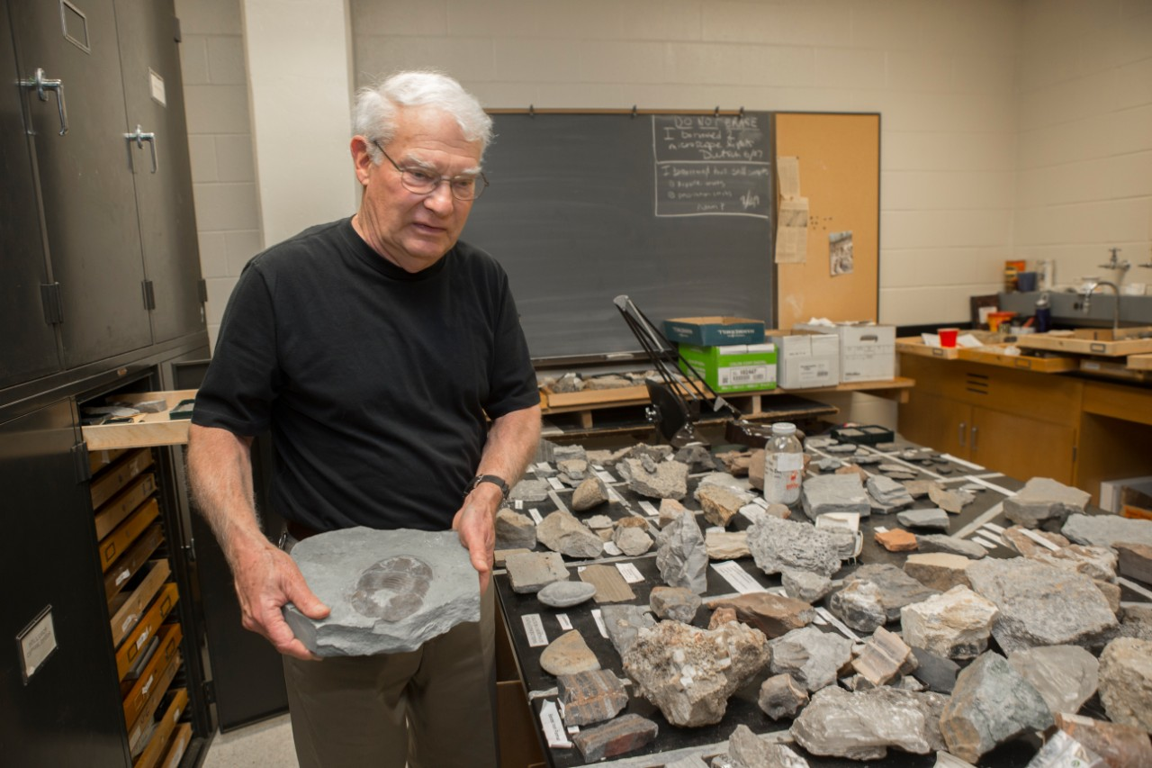 David Meyer carries a heavy rock with a trilobite fossil to a table covered in rocks in a geology lab.
