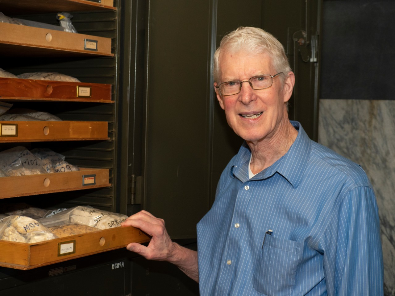 UC geology professor emeritus Warren Huff stands smiling next to a cabinet full of geology samples.