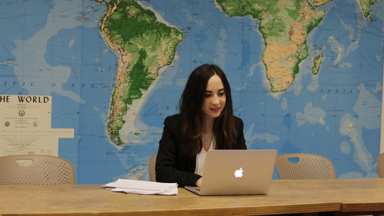 LLM student smiling in front of world map.