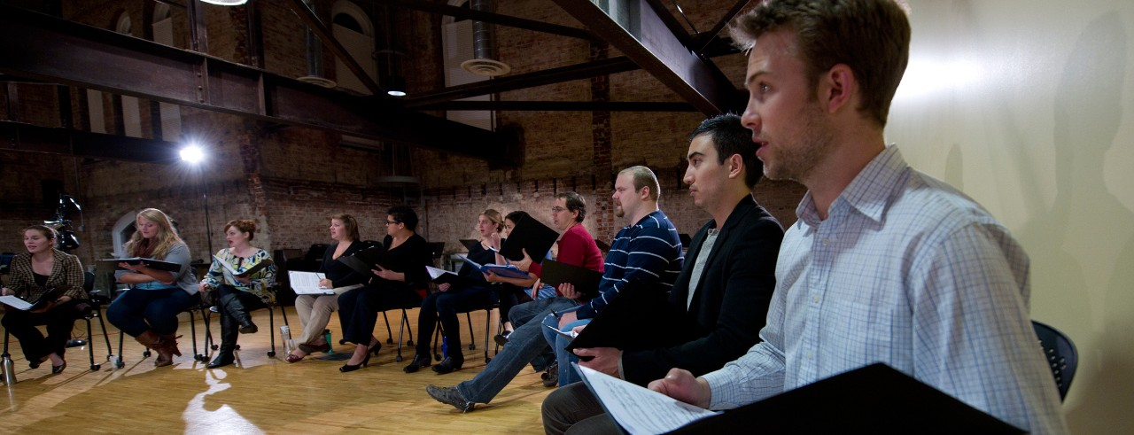 Singers sit in a circle with sheet music