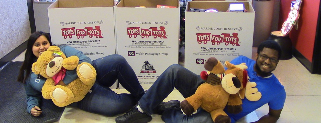 Two people pose with teddy bears and toy donation boxes