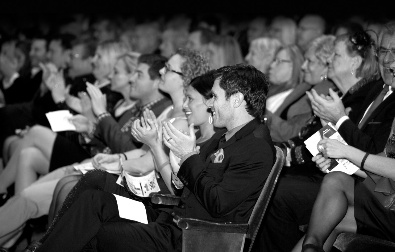A black and white photo of seated audience members applauding in CCM's Corbett Auditorium.
