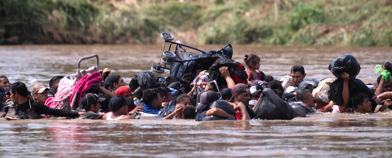 Migrants from Guatemala carry strollers and other belongings over their heads as they cross a deep river in Mexico.