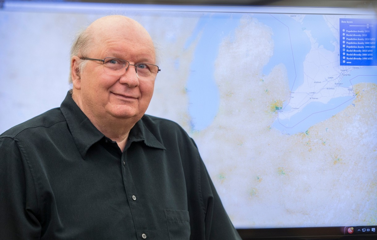 Tomasz Stepinski poses in front of one of his maps depicting the Great Lakes.