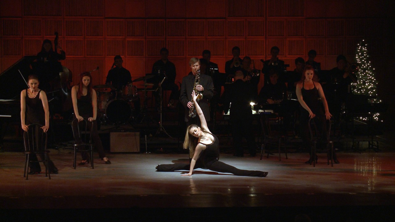 Dancers on stage with chairs, one in the spotlight doing the splits with musicians behind her