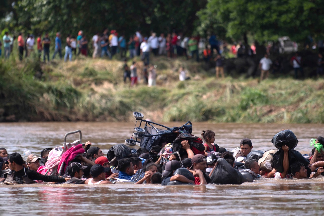 Central American migrants hold strollers, bags and other belongings over their heads while crossing a deep river.