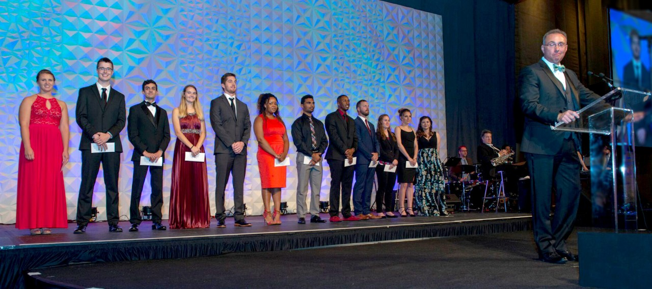 Students on stage receiving scholarships at gala