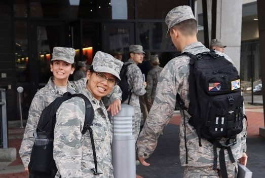 Two female cadets in camouflage battledress uniform stand outside the entrance of a building, smiling. Several other cadets in uniform are walking into the building in the background