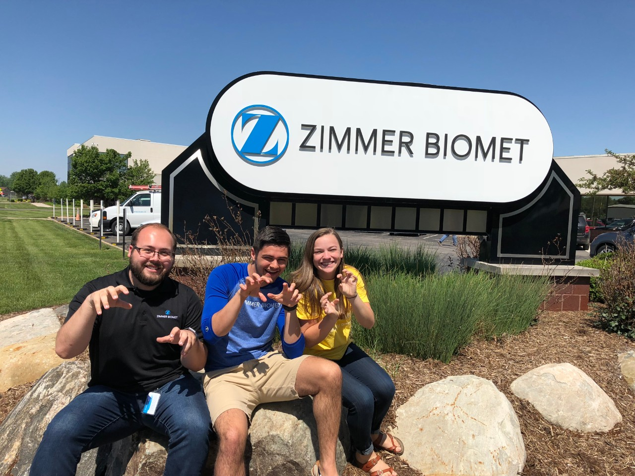Goodwin and two friends in front of Zimmer Biomet sign outside.