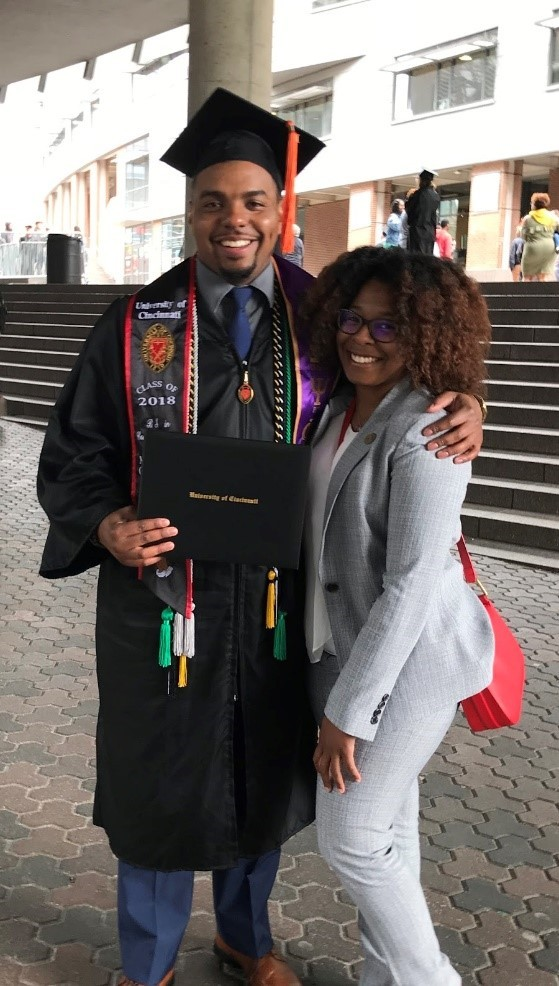 Male student in graduation cap, gown, and many honors tassels stands holding a diploma, outside Nippert Stadium with his arm around a woman