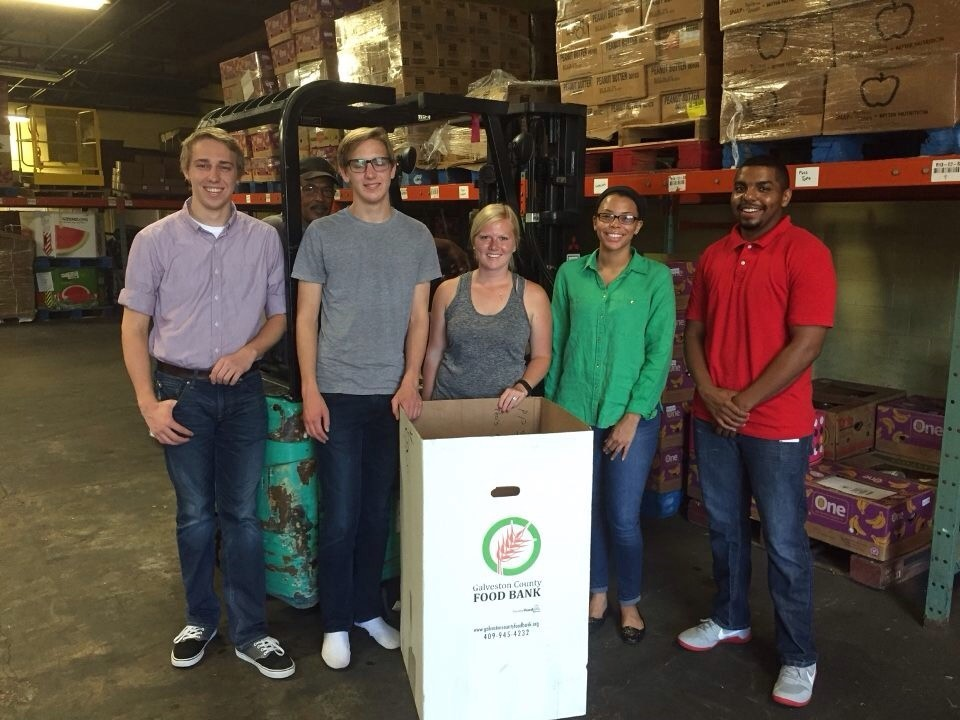 Five college-aged people stand behind a donation box inside a warehouse; a forklift and boxes on shelves are in the background