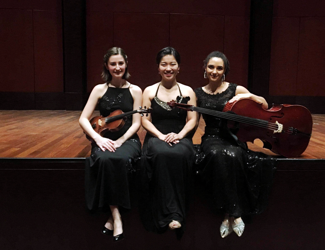 Shannon Lock, violin, Hyeji Park Miranda, piano, and Anita Graef, cello, sit on stage after their trio recital.