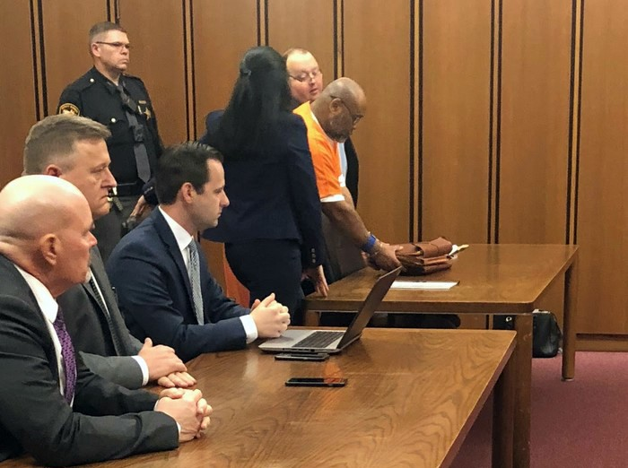Men in suits sit in a court room table while a defendant in an orange jump suit stands surrounded by his attorney at another courtroom table in a courtroom