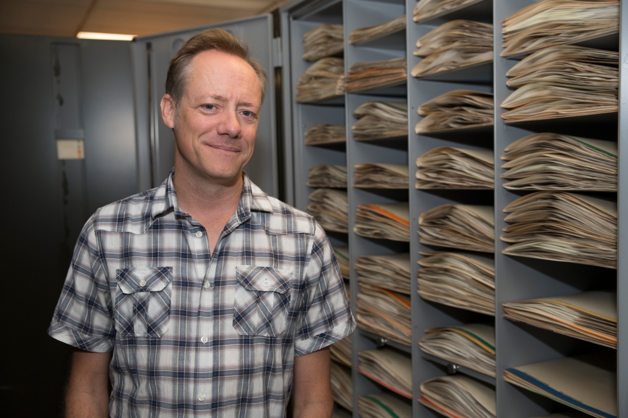 Eric Tepe stands in front of open cabinets containing folders of pant specimens.