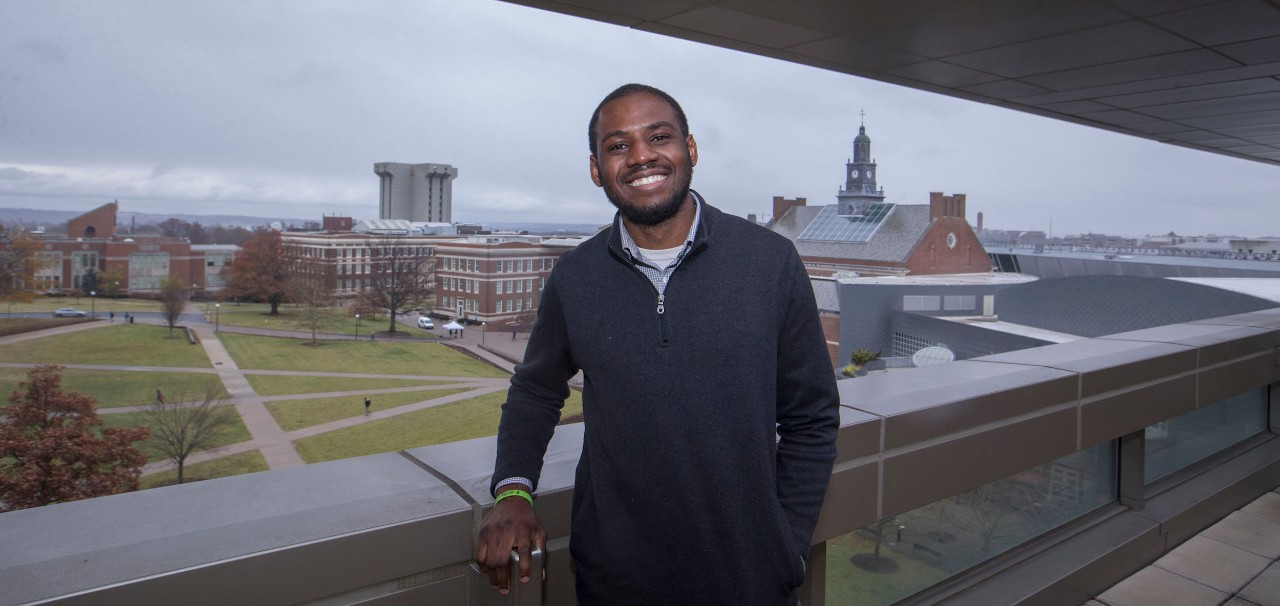 Serge Kikonda stands on 6th floor balcony in UC's Pavilion building.