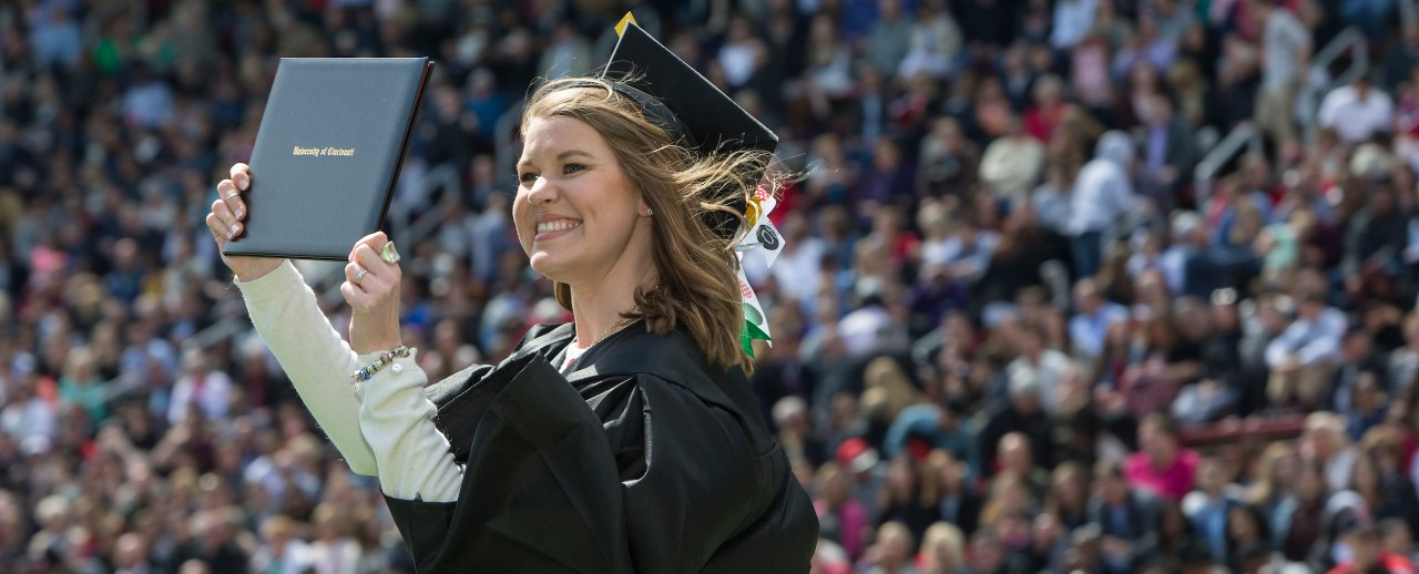 A jubilant UC graduate in a cap and gown waves her diploma for supporters to see as she leaves the stage.