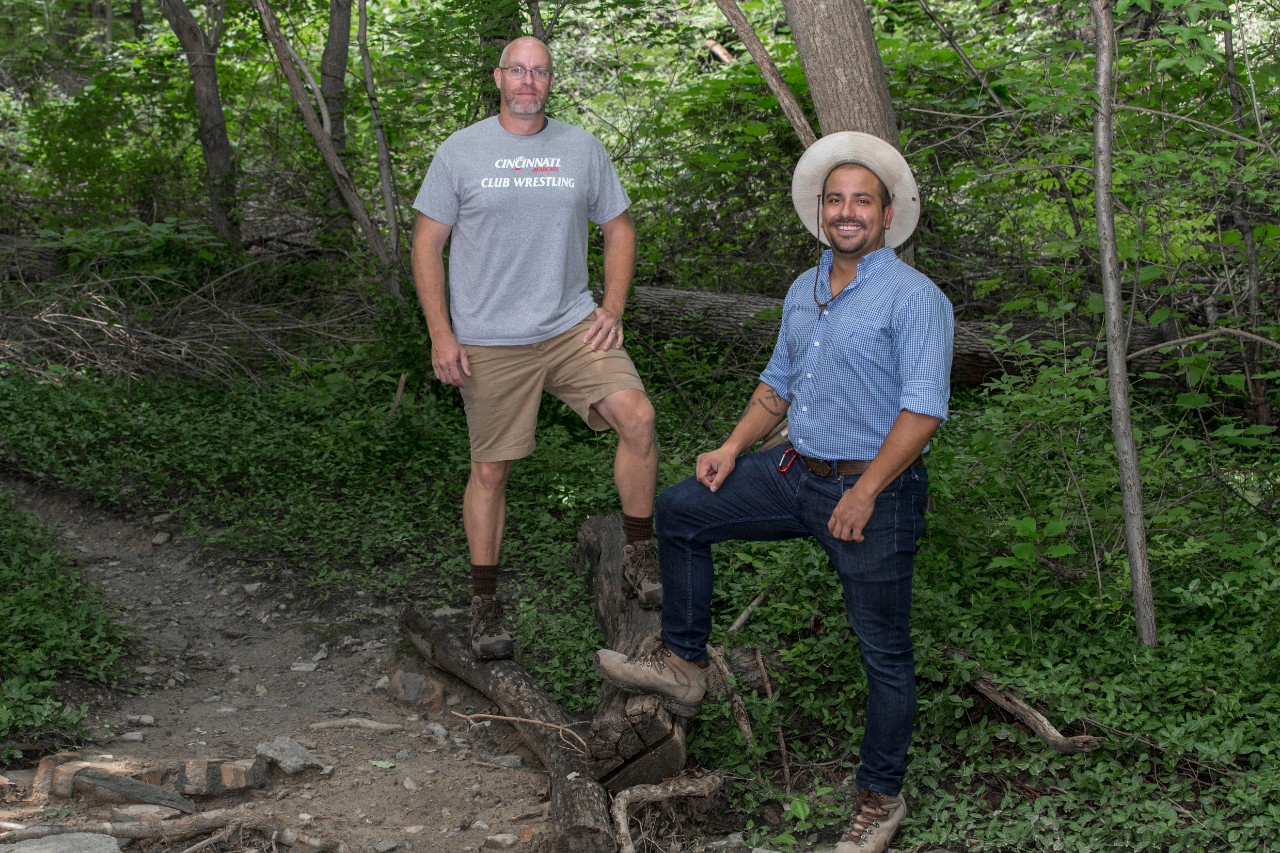 Chris Atchison and Ivan Carabajal pose for a photo in a forested area.