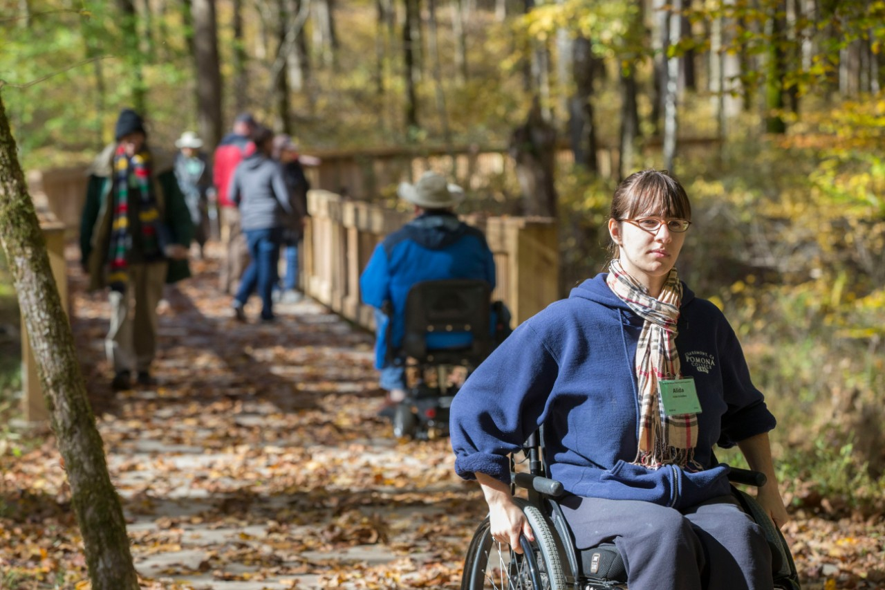 A woman in a wheelchair takes a photo with her phone inside Mammoth Cave