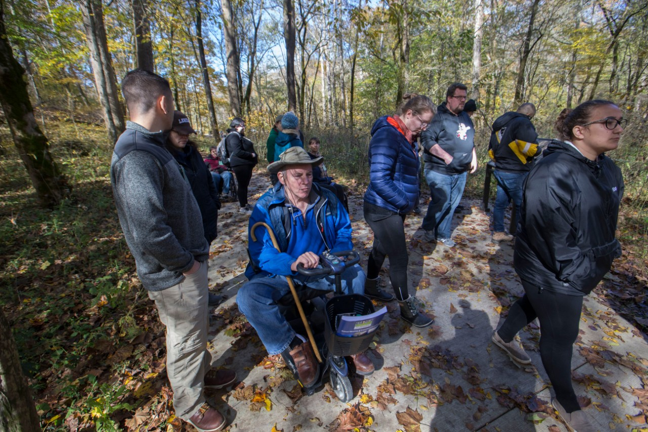 IAGD members explore the new accessible walking path in a forested area of Mammoth Cave National Park