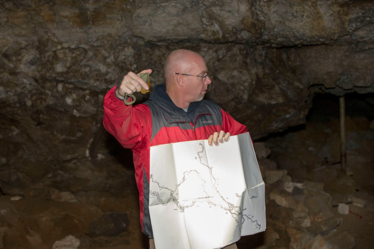 Chris Atchison, a while male wearing a red jacket, inside a cave holding a map.