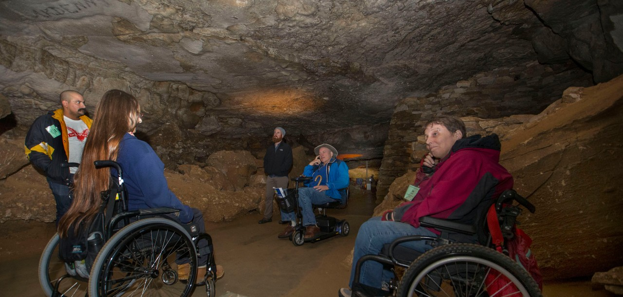 A woman in a wheelchair takes a picture of cave writings inside of Mammoth Cave