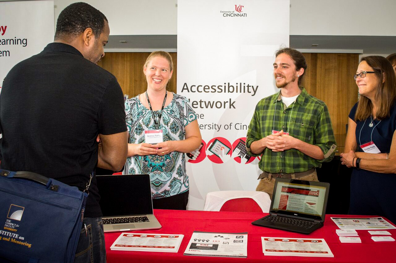 Accessibility Network members talk with faculty around a booth.