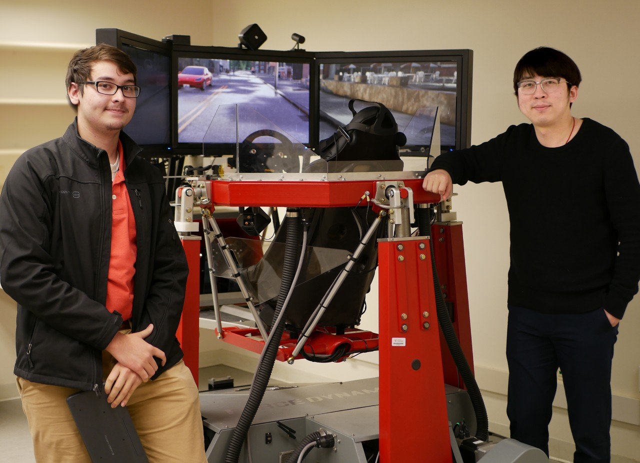 Ma and UC student Andrew Greer stand beside the simulator