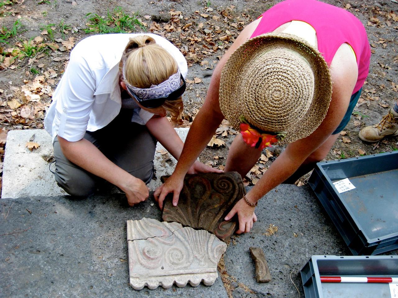Two women kneel over Roman tablets