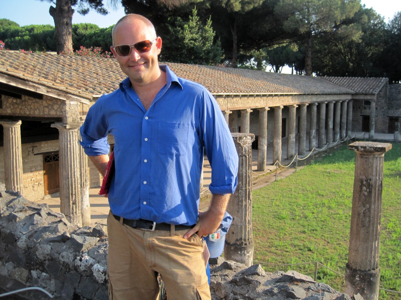 A man in a blue shirt and khakis stands in front of Roman ruins
