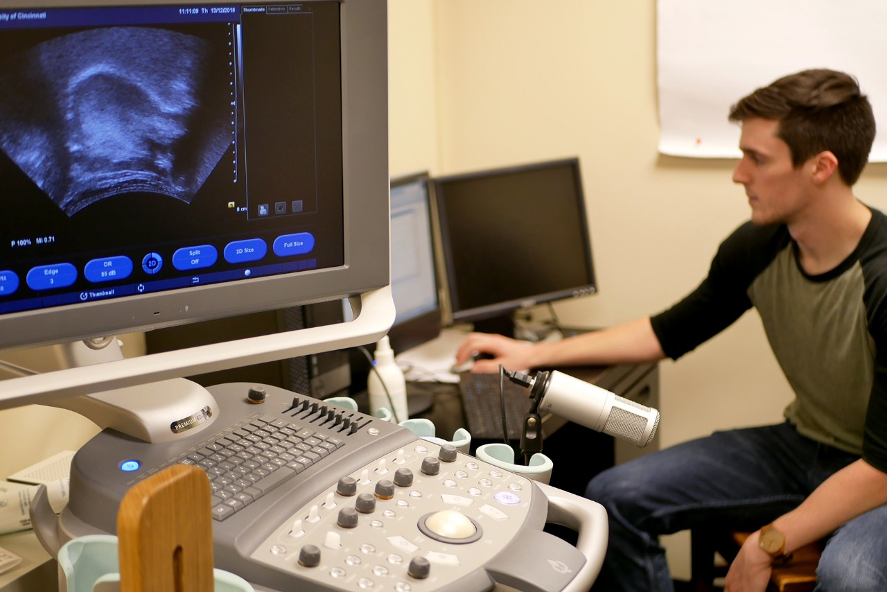 Masterson working on computer in lab with ultrasound machine in foreground