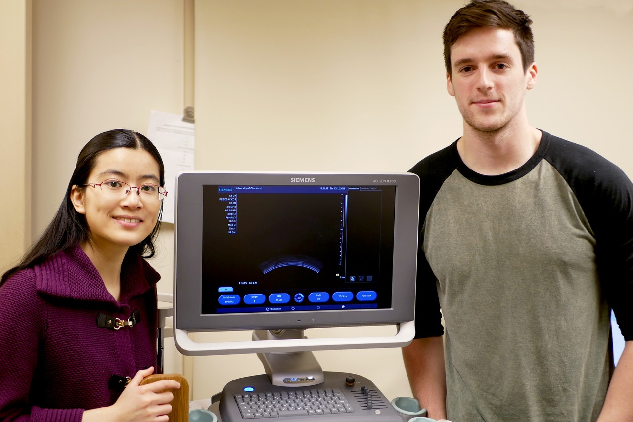 Li and Masterson stand with ultrasound machine.