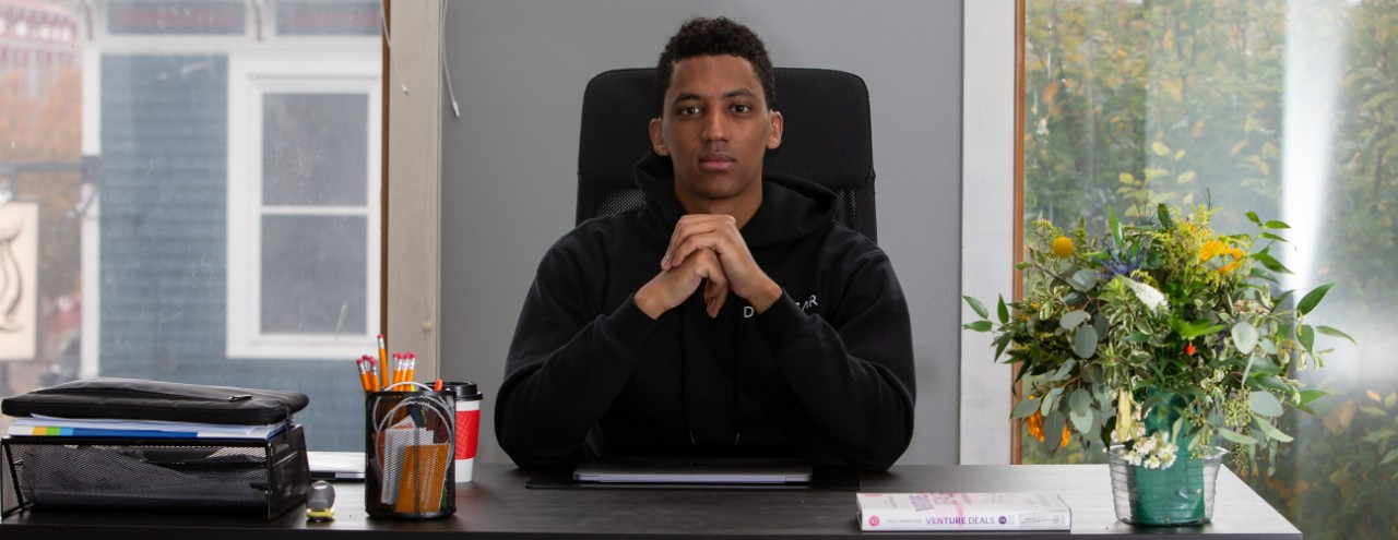 Aman Tsegai sits at his office desk with his hands folded in front of him.