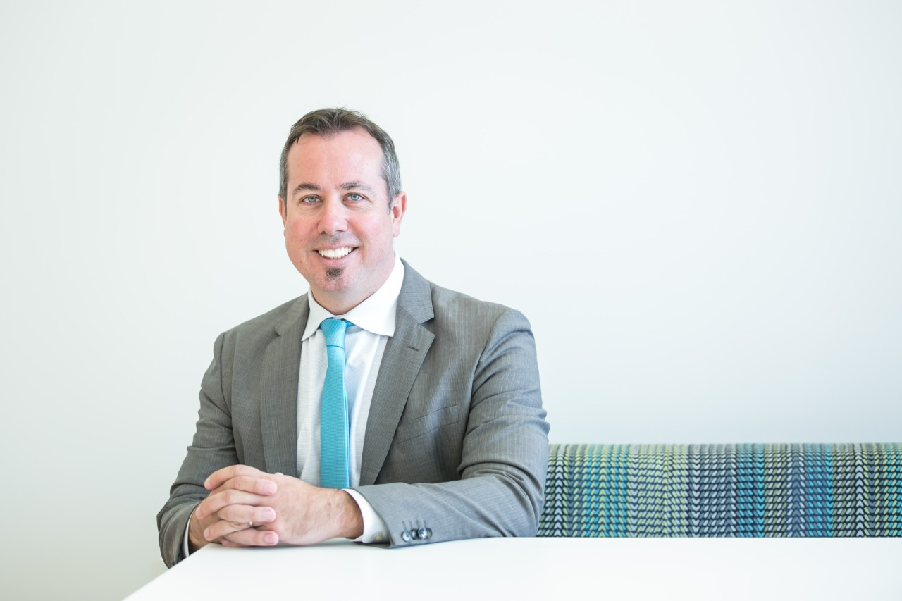 Dean Neil MacKinnon, PhD, sitting in a chair