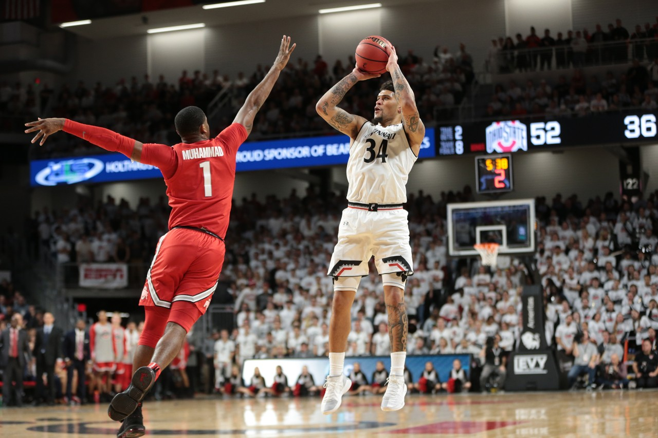 A UC men's basketball player in a white uniform shoots the ball over the outstretched arms of an Ohio State player in a red uniform at Fifth Third Arena.