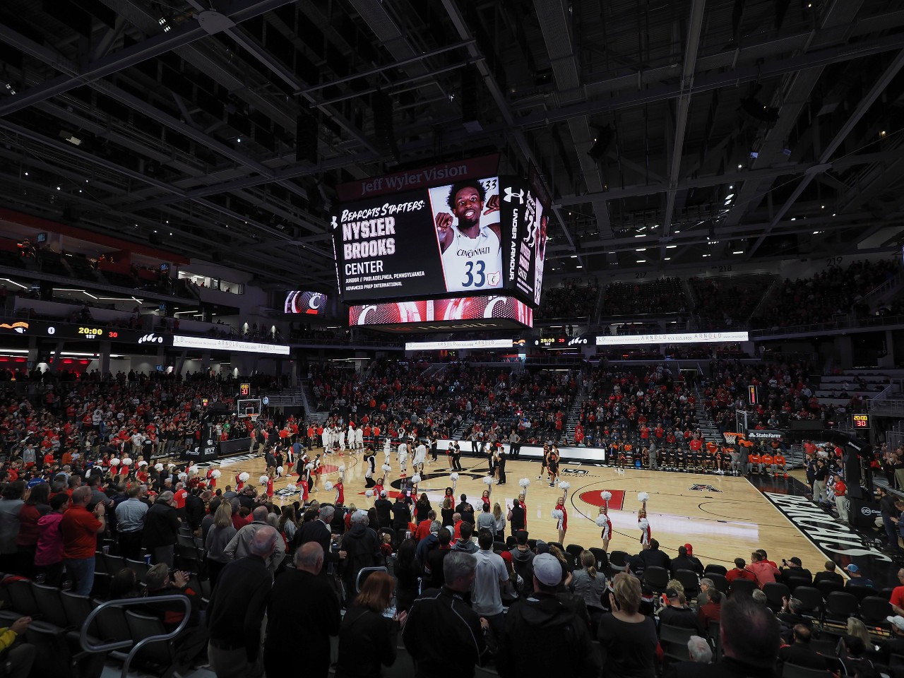 A wide shot of Fifth Third Arena during a men's basketball game shows the giant four-panel scoreboard, the UC logo at center court and a packed house of fans.