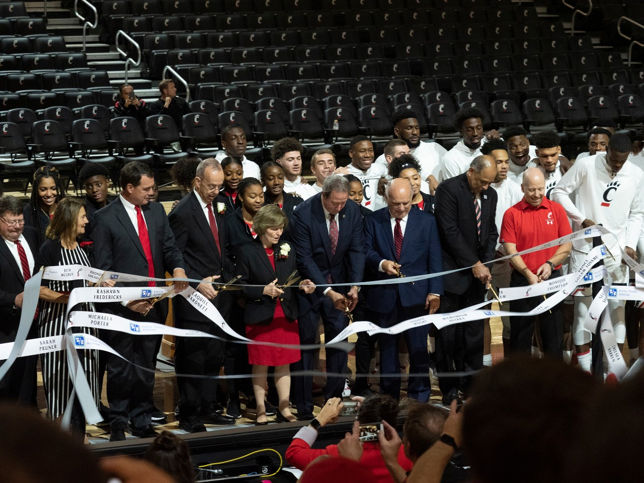 A large group of people gathers at center court of Fifth Third Arena to cut a big ribbon.