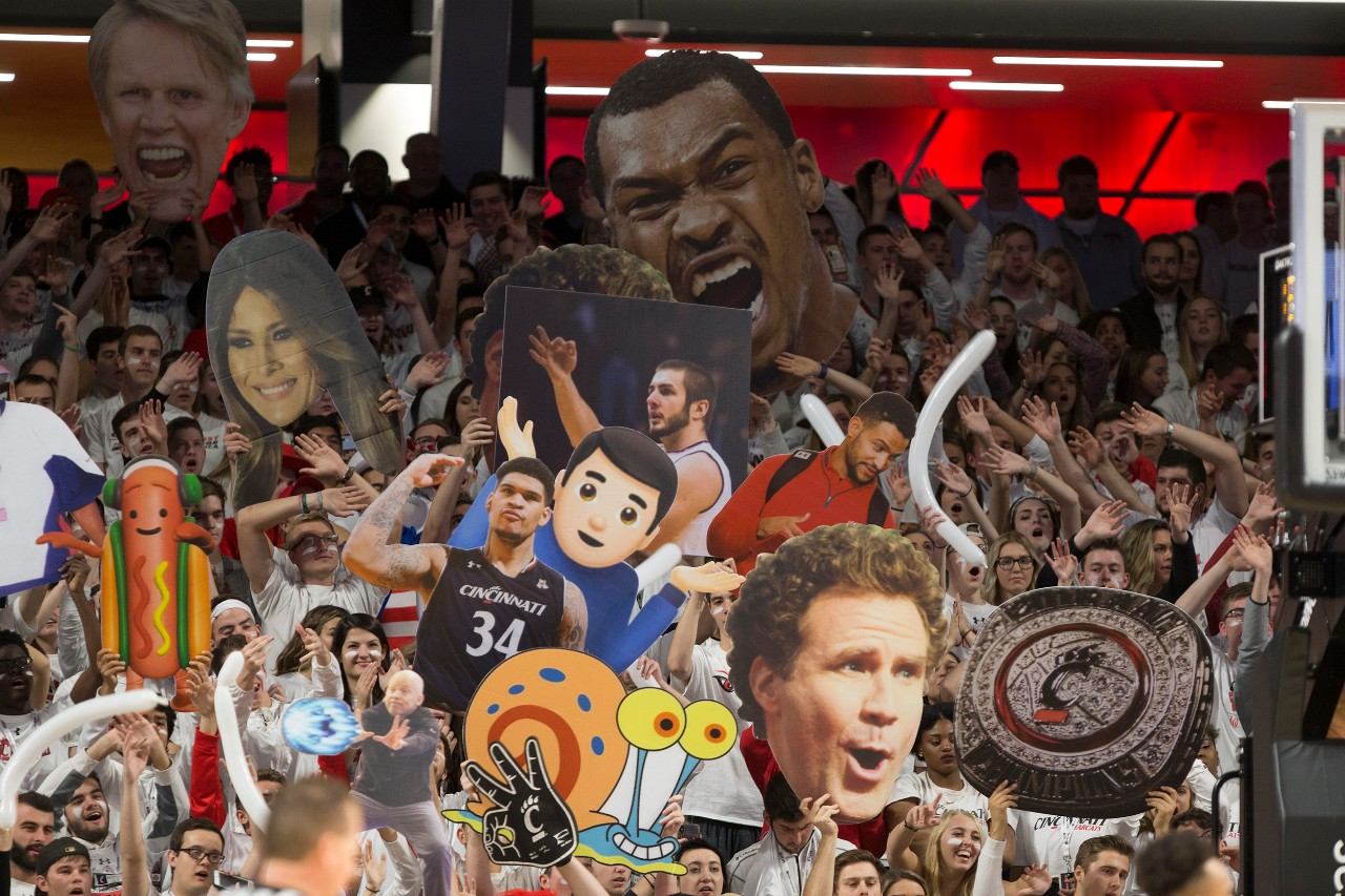 UC fans in the student section of Fifth Third Arena hold up signs and banners and cheer their team.